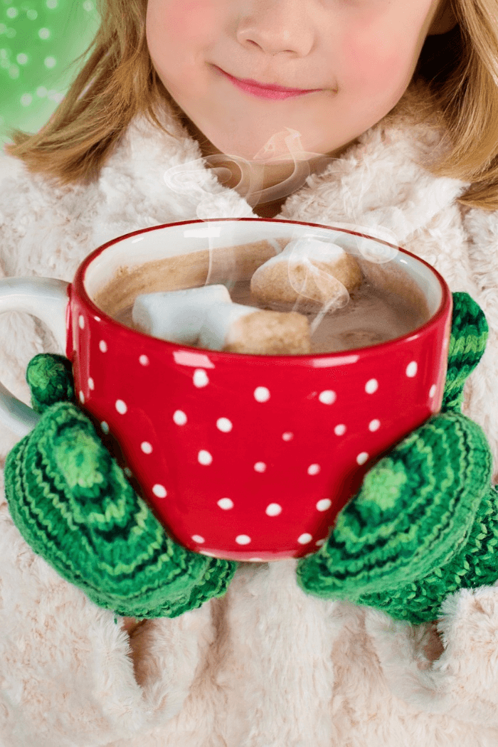 Little girl with green gloves holding a red mug of hot chocolate