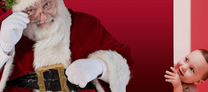 Santa Claus sitting with a child peeking around the corner at him
