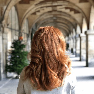 Red Headed Woman in a walkway with stone arches and a green Christmas Tree