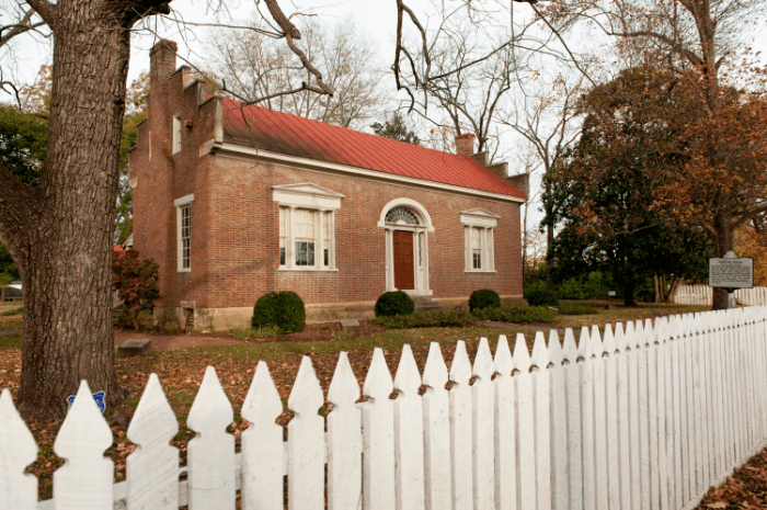 The front of a small red brick home with a white picket fence in front