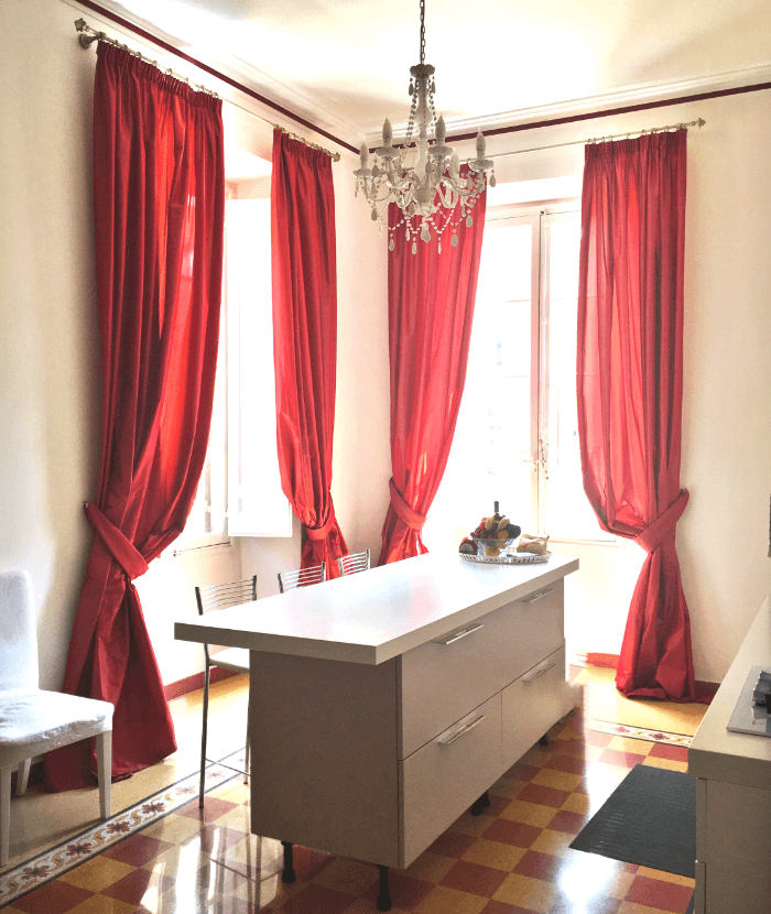 A Kitchen counter with red curtains in one of the apartments in Europe