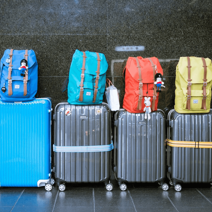 A row of four suitcases with colorful backpacks balanced on top