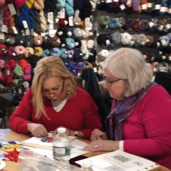 Patricia Sone and Lori Whitlow working on a needlepoint canvas