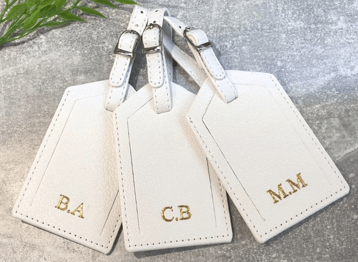 three white luggage tags