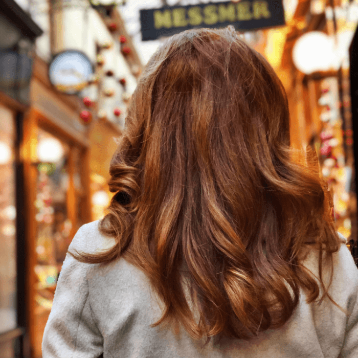 Woman with long red hair pictures from behind looking down a long hall