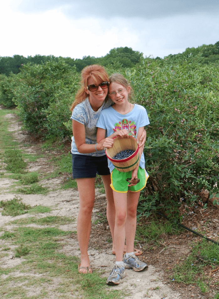Mother and Daughter holding a bucket of blueberries in a row of blueberry plants