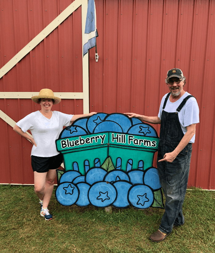 Woman in a white shirt and a man in overalls and a baseball hat posting with a wooden blueberry sign