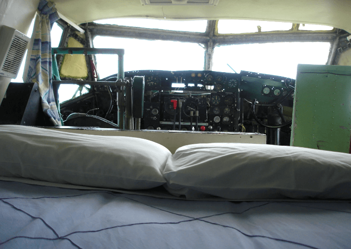 a bed and two pillows inside the cockpit of a plane