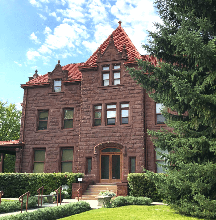 Old two-story brick home under a blue sky