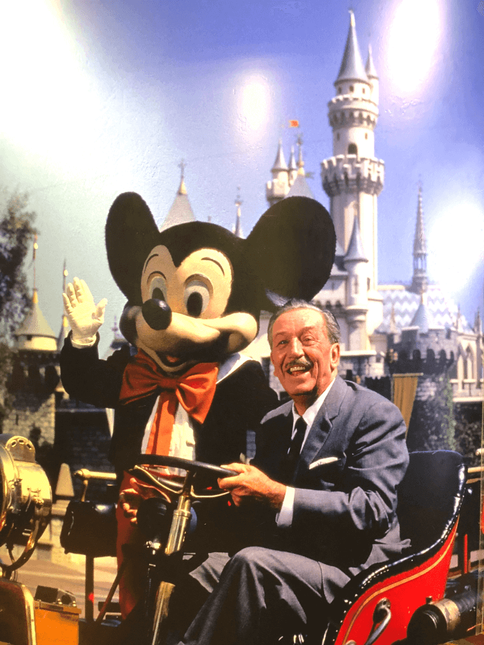 Walt Disney and Mickey Mouse waving and posing for a picture sitting in a red car with a castle in the background