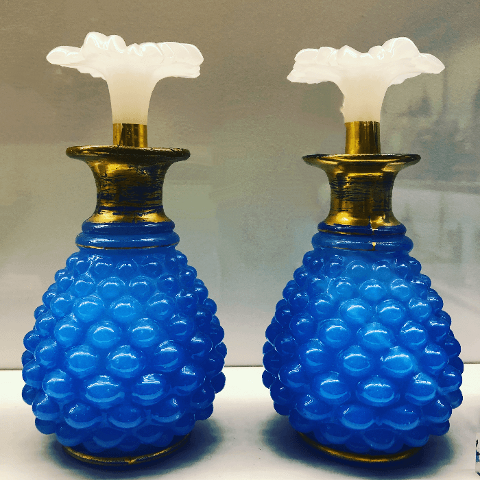 Two bright blue glass perfume bottles with white flower shaped tops in the Decorative Arts Museum Paris