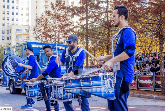 four men in blue shirts playing the drums in the Dallas Christmas Parade