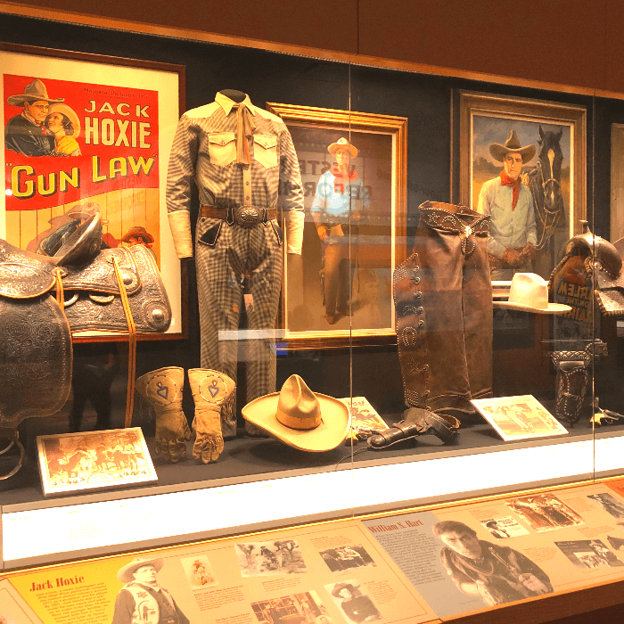 Western Movie posters and cowboy hats in a display cabinet in the National Cowboy & Western Heritage Museum