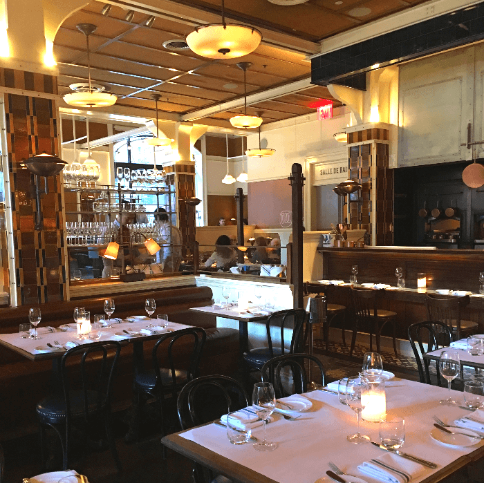 a restaurant with tables set with white tablecloths and wine glasses