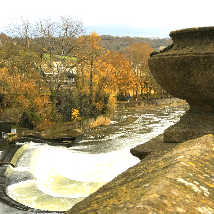 an old sone bridge looking over a rushing river