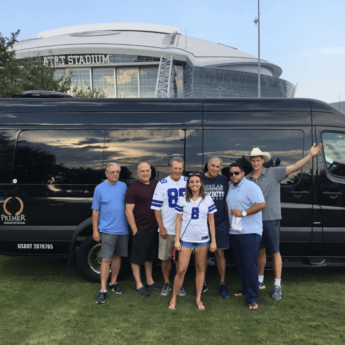 a group of people in Dallas Cowboys jerseys standing in front of a black mini bus