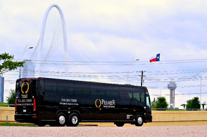 a black motor coach with the Texas Flag in the background
