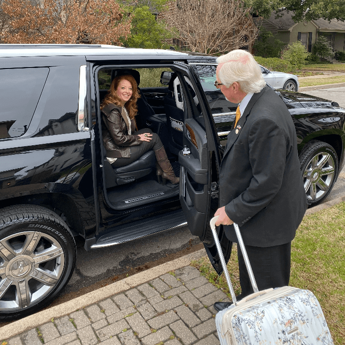 man in a dark suit opening the door of a black SUV with a women sitting inside