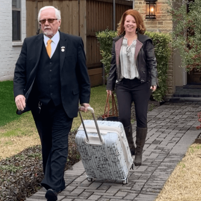 a man in a black suite pulling a white suitcase with a woman walking behind him