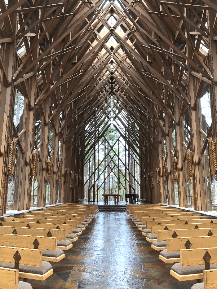 a glass and wood chapel in the woods