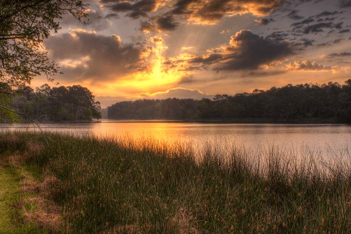 a sun setting over a lake