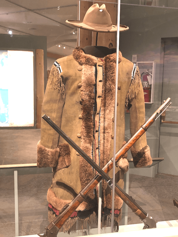 a brown buckskin coat in a glass case