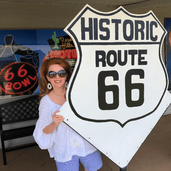 woman with red hair posing behind a large Route 66 sign