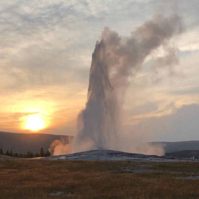 Old Faithful erupting at sunset