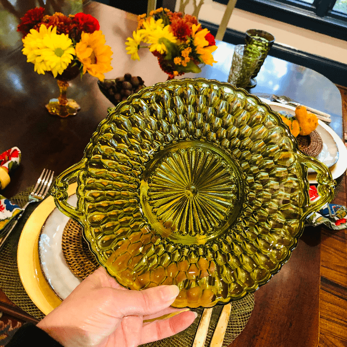 a hand holding a green pressed glass plate
