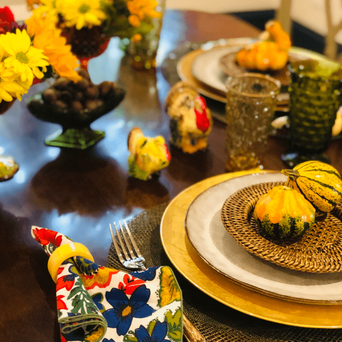 a dining room table set with flowers and gourds