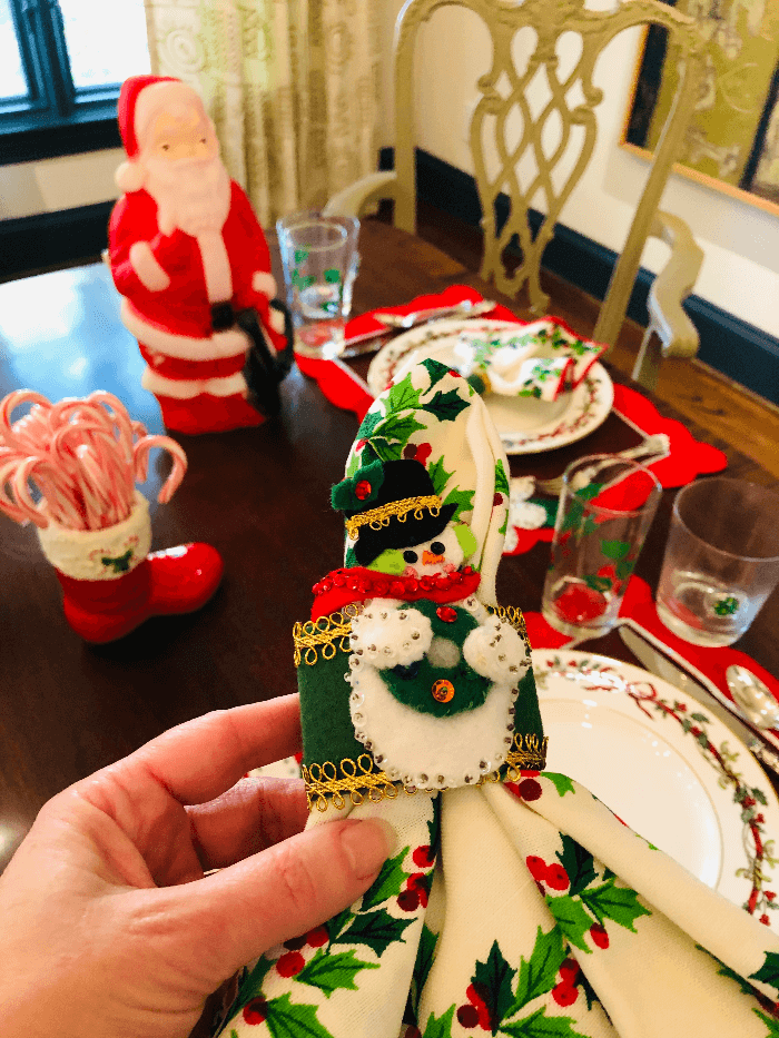a hand holding a sequined snow man napkin ring