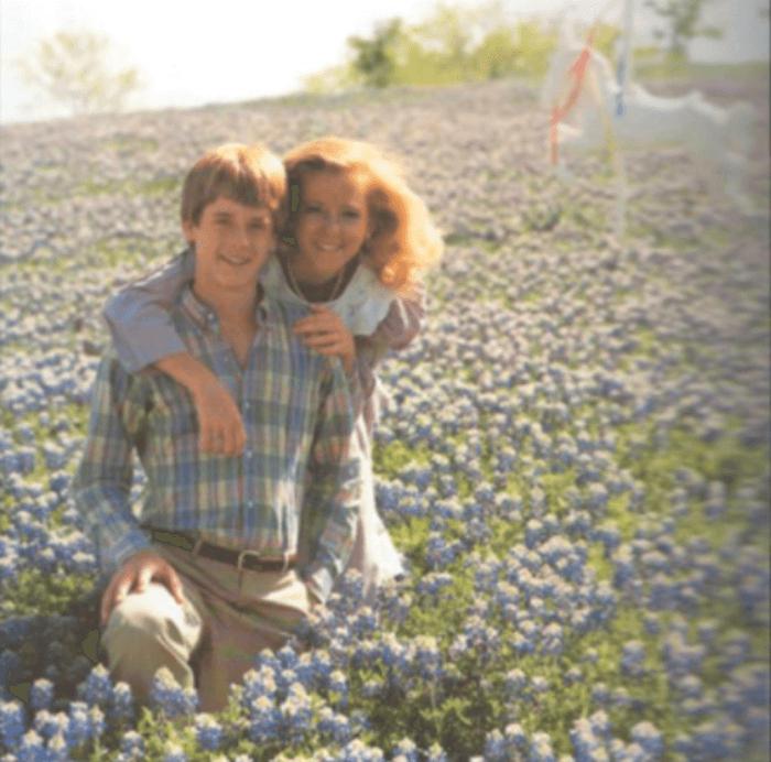 a boy and a girl kneeling in a field of Bluebonnets