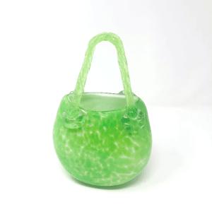 a green glass vase shaped like a purse