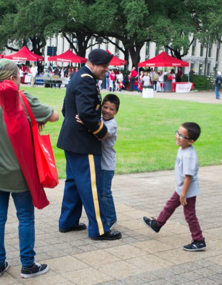 A soldier is greeted by a child with a hug. | Sara Samora/The Cougar