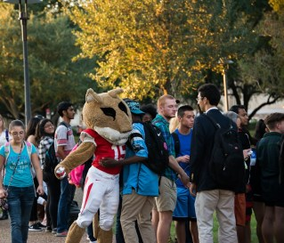 Shasta hugs UH students during the pep rally.
