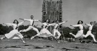 UH cheerleaders dancing mid-leap around an unlit bonfire in 1969. |Courtesy of UH