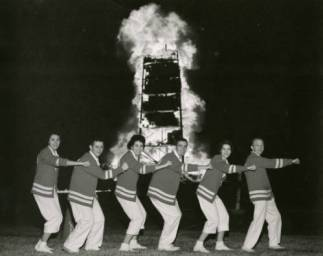 Cheerleaders make a line in front of a lit bonfire. | Courtesy of UH