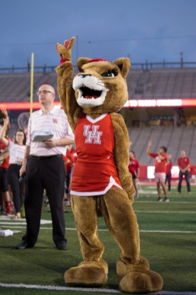 Mascot Sasha holds her cougar paw high during the playing of the alma mater by the Spirit of Houston Marching Band. | Trevor Nolley/The Cougar.