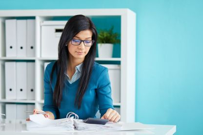 57152361 - young businesswoman with glasses calculates tax at desk in office