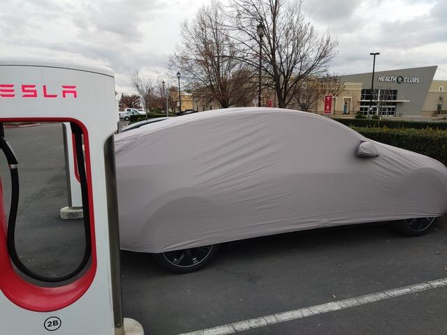 Tesla Model Y covered at supercharger.