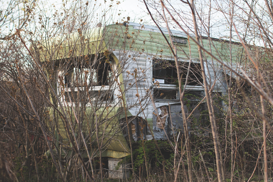 green trailer, abandoned, overgrown