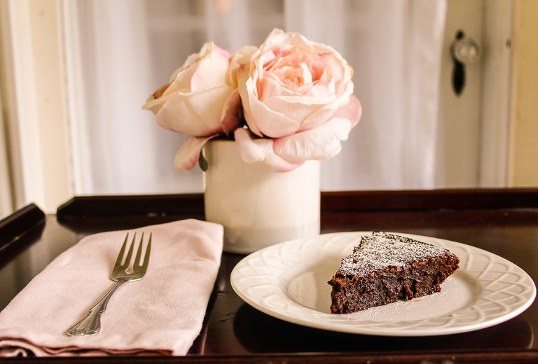 A piece of flourless chocolate cake sits on a white plate next to a vase of pink flowers and a pink napkin with a fork lying on it.
