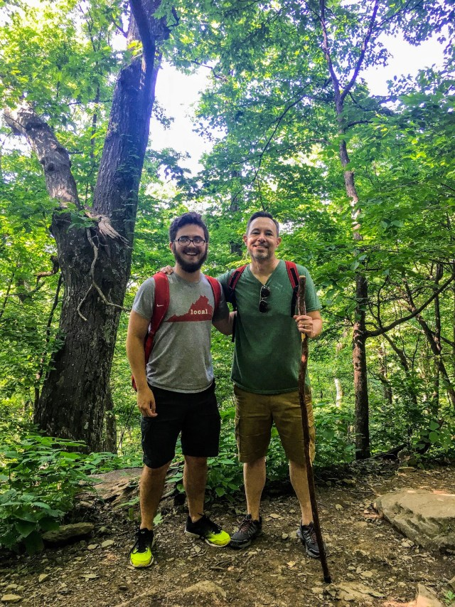 two men with backpacks in the woods-- gifts suggested for this guy are things such as an insulated backpack, down jacket, or paracord bracelet