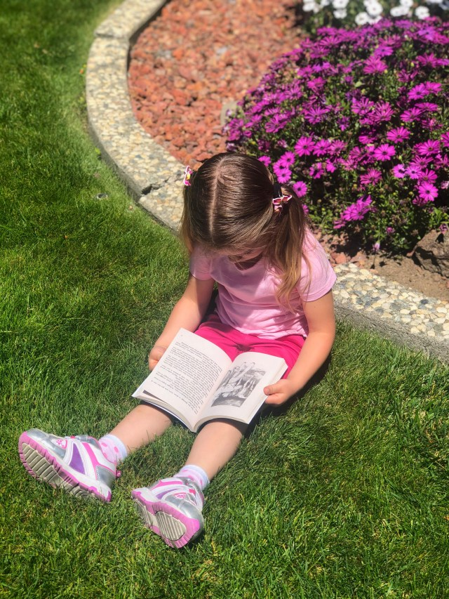 little girl sitting in the grass reading a book