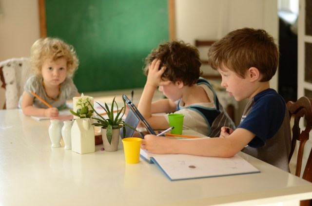 three children doing schoolwork at a table