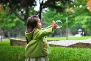 Young girl playing with bubbles