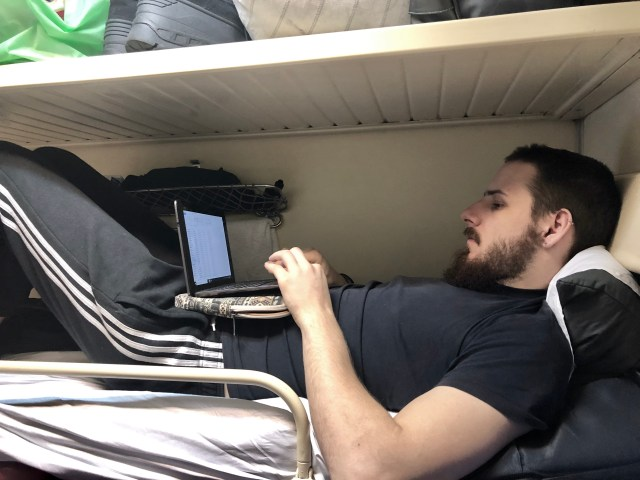 Boy hunched over on a laptop on his top bunk in the Trans Siberian Railway Carriage  Exactly What to Expect from the Trans Siberian Railway www.thedancingcircustraveller.com