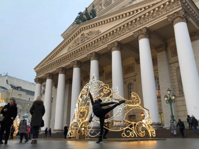 Girl doing arabesque in front of the Bolshoi Ballet Theatre