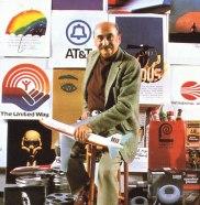 Saul Bass seduto su uno sgabello contornato da alcune delle sue creazioni