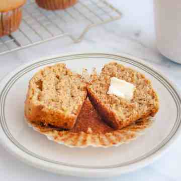 Bran muffin cut in half with butter on a white plate with more muffins and coffee cup in background